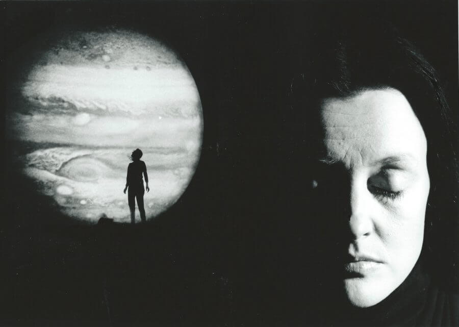 Black and white promotional image for Night Sky showing a planet on the left with a person silhouetted against it and the face of a woman with her eyes closed on the right