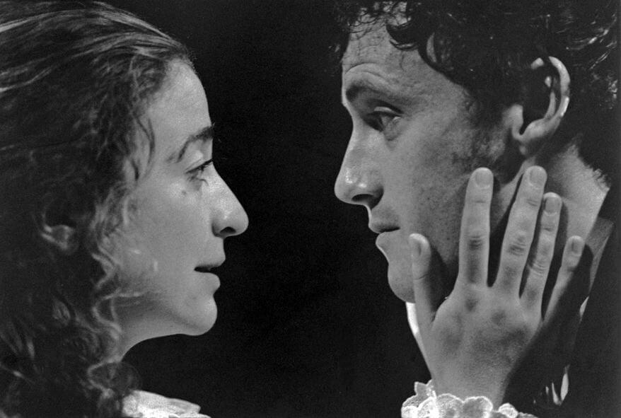 Black and white image from The Clearing showing a close up of a woman and a man's faces. They are looking at each other and the woman has her hands on the man's face