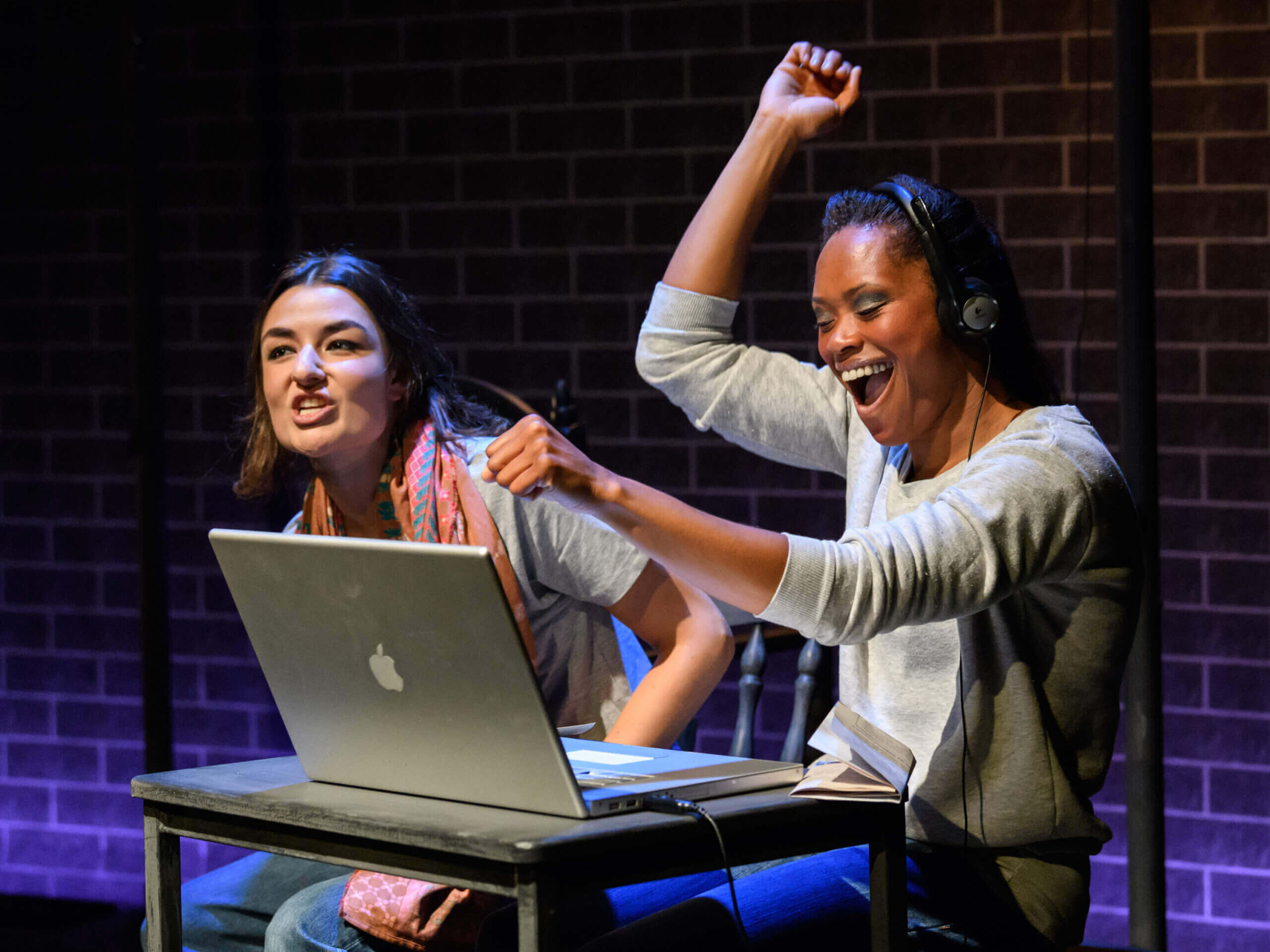 The Last Queen of Scotland production image showing two women are cheering while sitting at a table with a laptop on it