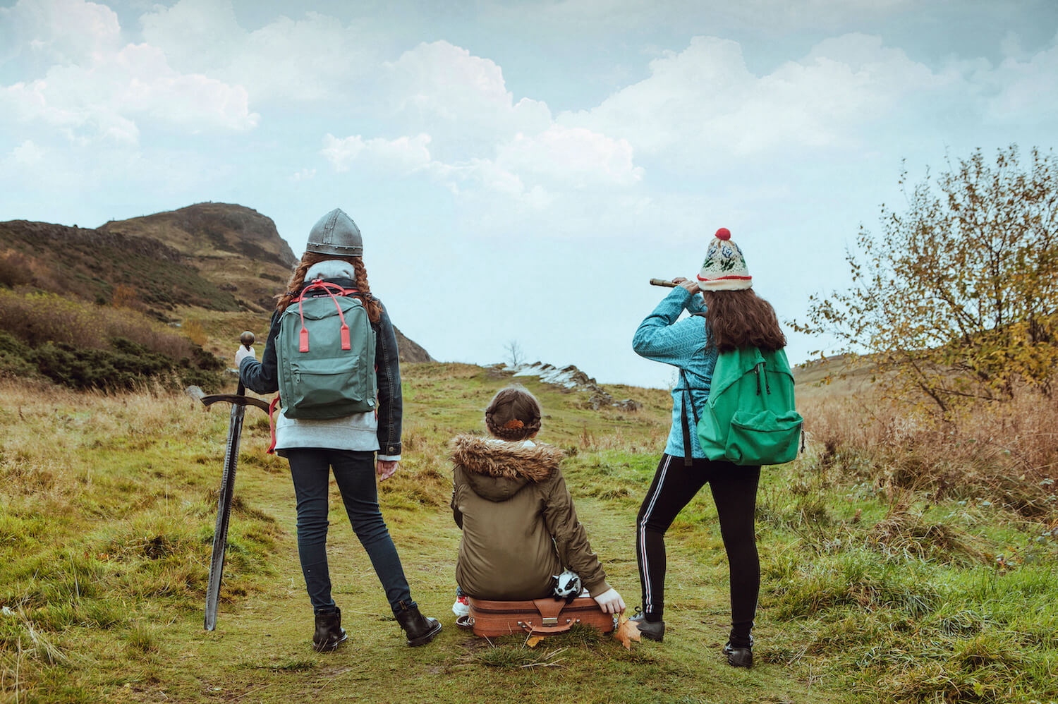 This Girl promotional image showing three girls dressed in outdoor gear out in the hills, one is looking through a telescope, image take from the back
