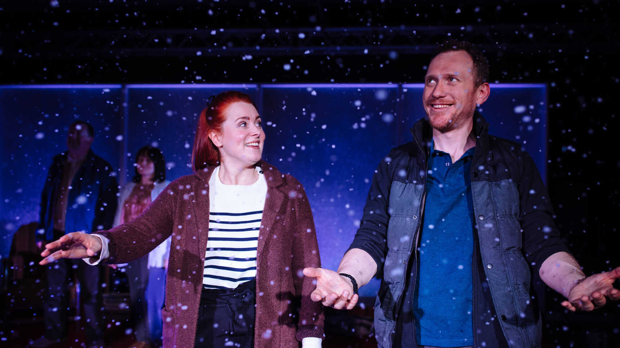 Fibres Film production image of Suzanne Magowan and Ali Craig standing with their arms outstretched as snow fall around them