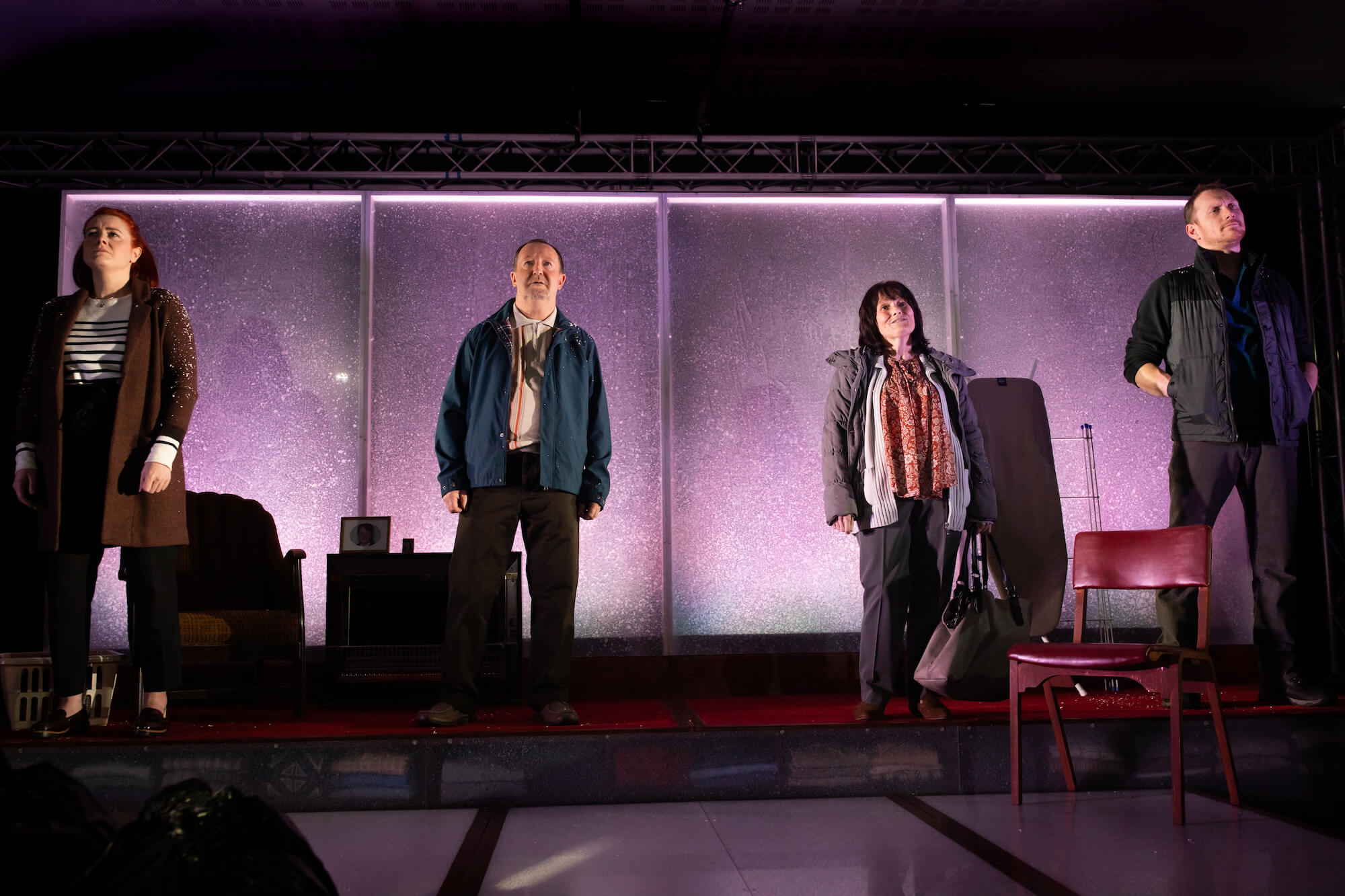 Fibres Film production image of Suzanne Magowan, Jonathan Watson, Maureen Carr and Ali Craig standing in a line on stage looking serious