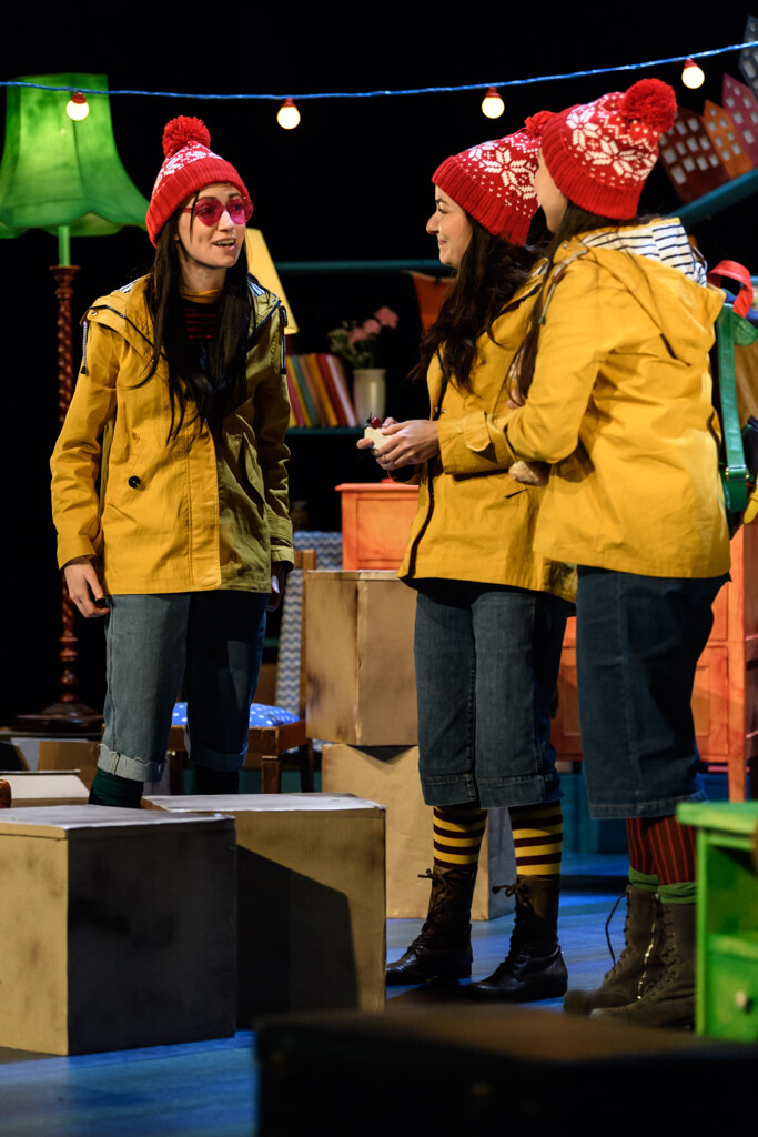 This Girl production image showing three girls standing on stage together, wearing red bobble, hats and yellow rain jackets