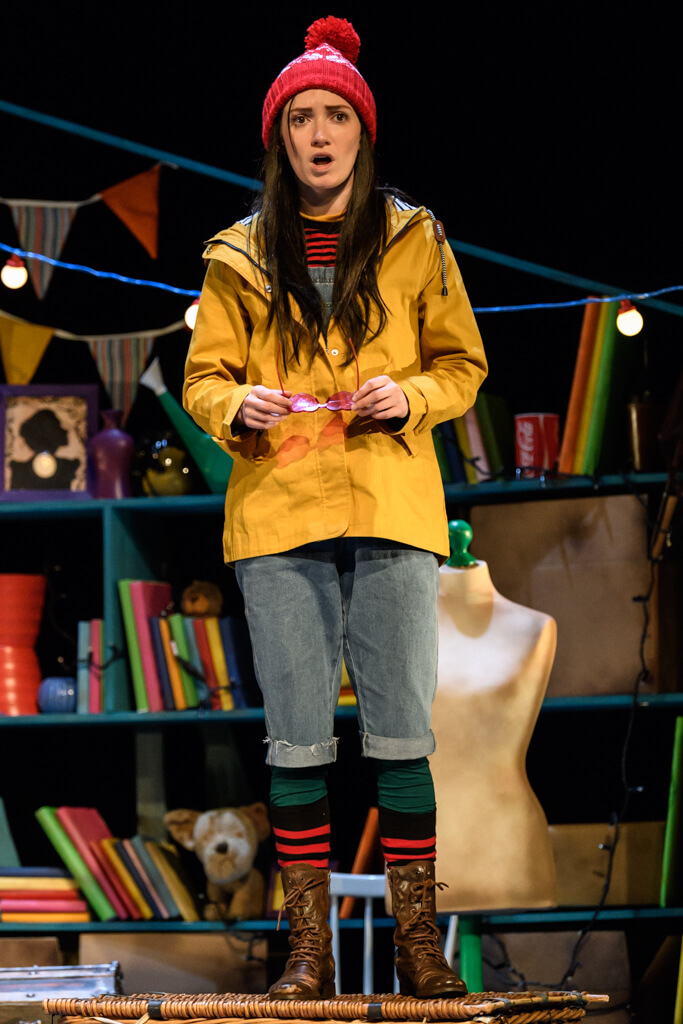 A girl stands and looks shocked. She is wearing a yellow anorak, red bobble hand, blue jeans and brown boots stands on a colourful stage