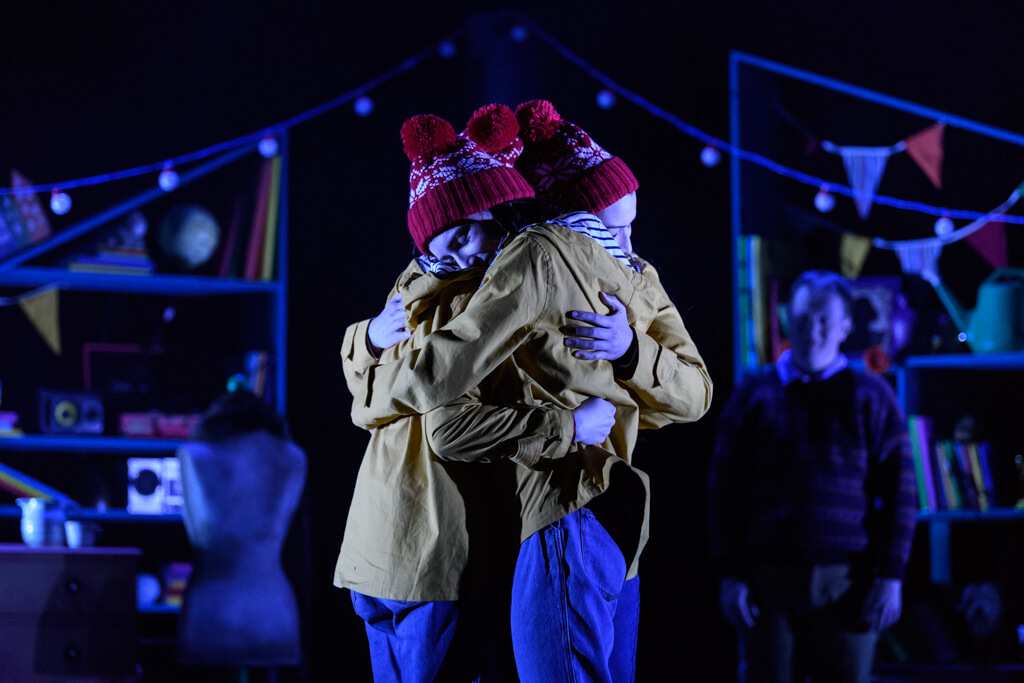 Three women hugging dressed in yellow raincoats and red bobble hats on a dimly lit stage.