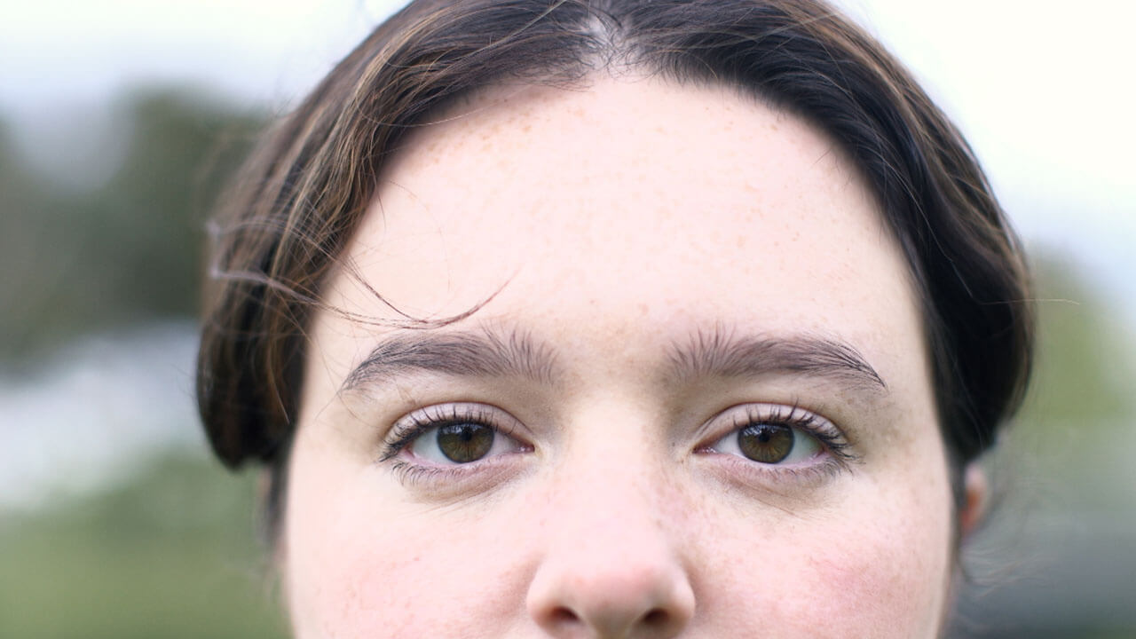Film Still from the short film Masquerade. close up of the top half of a woman's face with her staring intently at the camera.