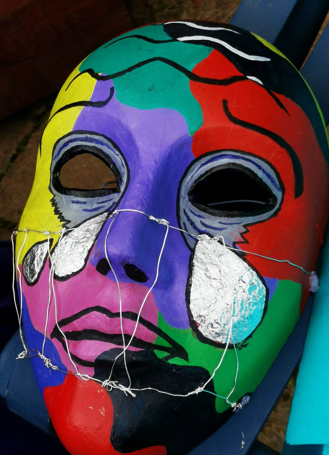 Brightly colour paper mask with tinfoil teardrops and wire over the nose and mouth