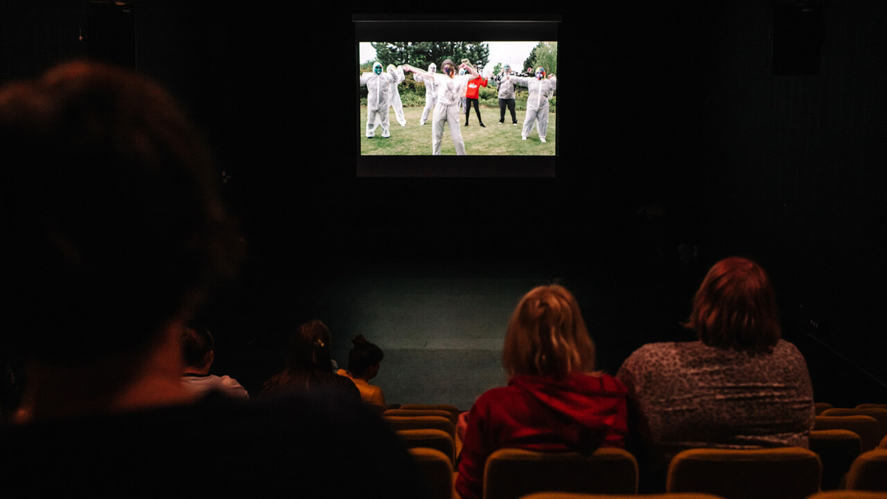 Inside the auditorium at the screening of the film Masquerade at North Edinburgh Arts - the film is playing on the screen and women are socially distanced in the raked seating. the photo is taken from the back of the performance space.