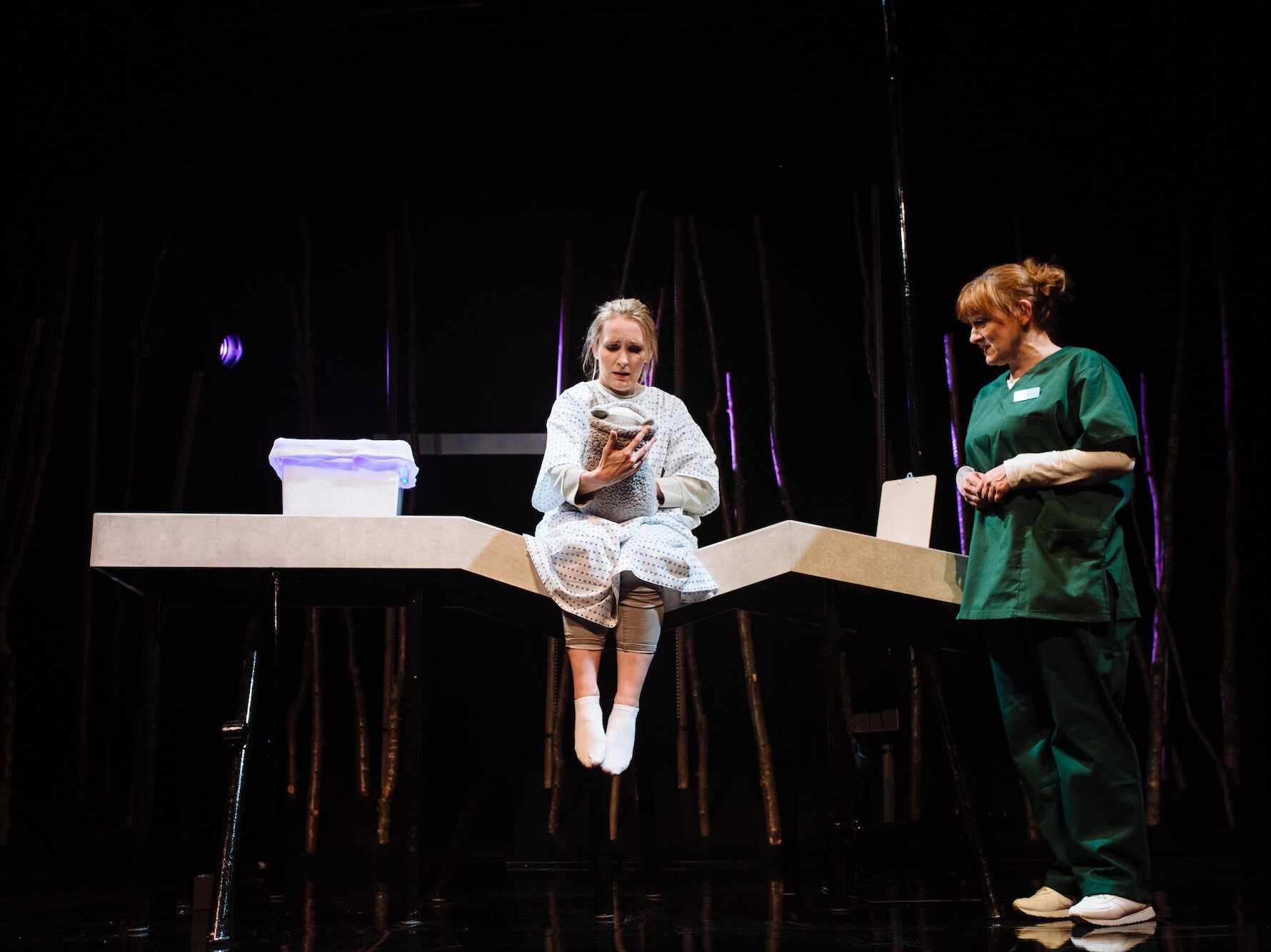 Hope and Joy production image showing a woman in green scrubs standing next to a woman in a hospital gown sitting on the edge of a bed holding a teddy