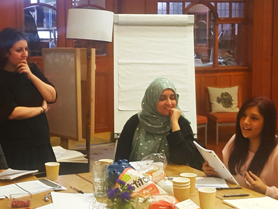 Muslim Women's Stories project participants sitting around a table in the Glasgow Women's Library sharing their writing