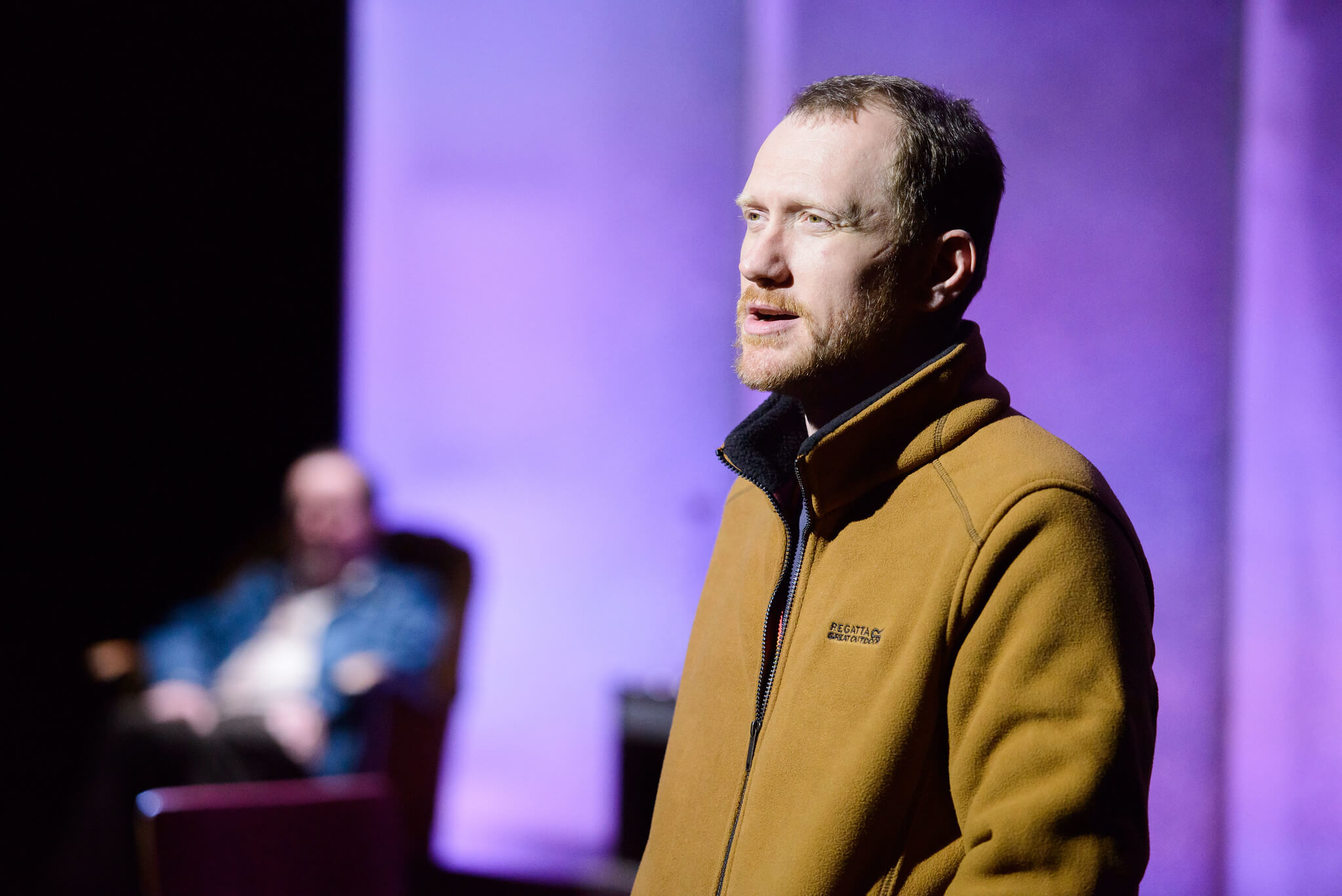 Fibres Film production image showing Ali Craig well lit on stage with Jonathan Watson sitting out of focus in the background