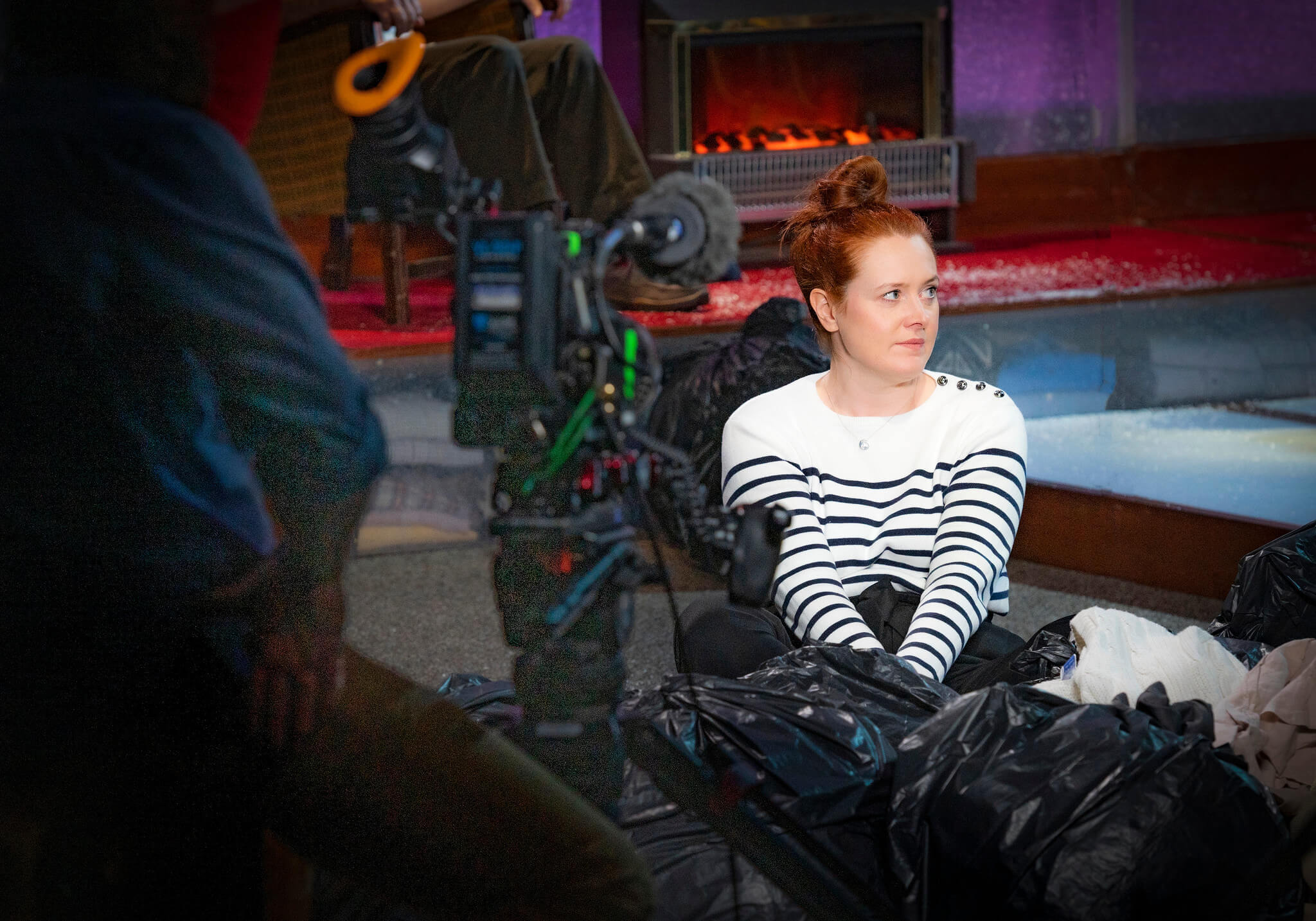 Rehearsal image for Fibres films showing Suzanne Magowan sitting on set and being filmed