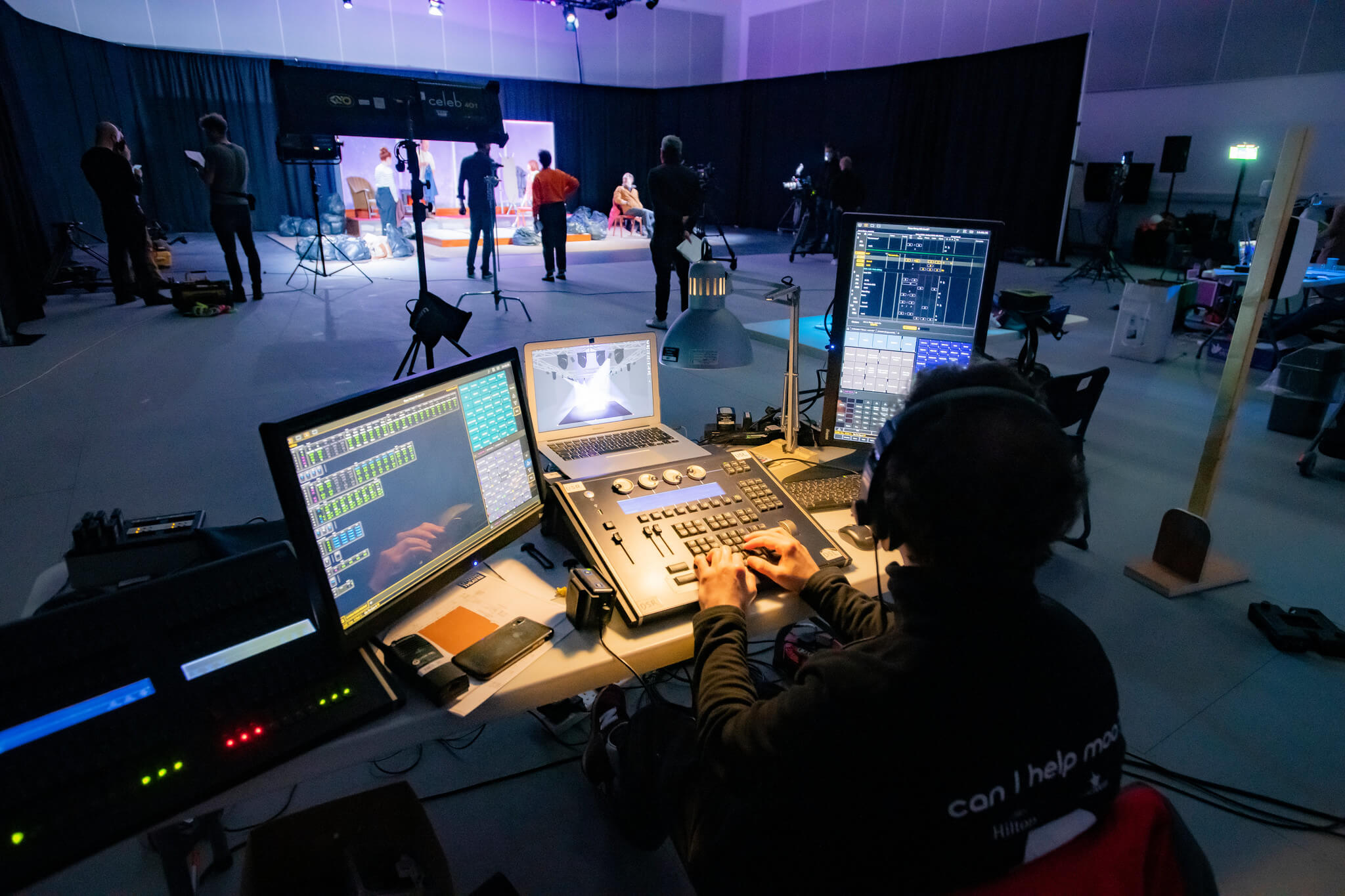 Rehearsal image for Fibres films showing the recording desk and the stage set being filmed in the background