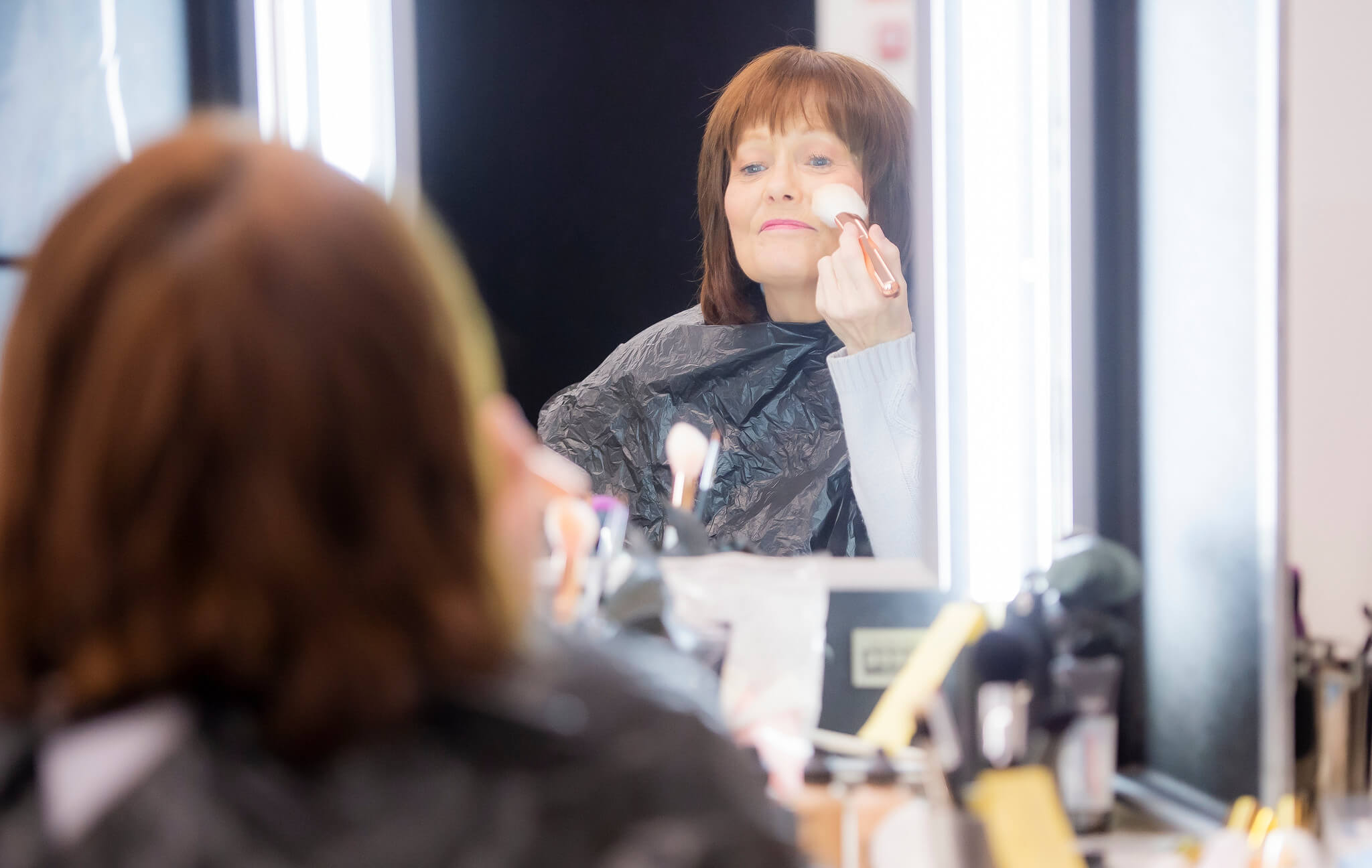 Rehearsal image for Fibres films showing Maureen Carr doing makeup in front of a mirror