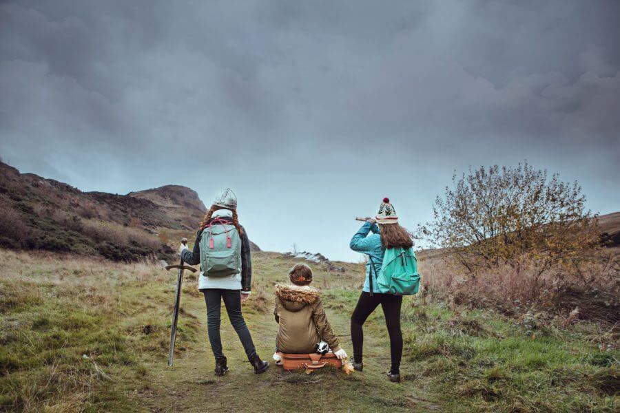 Three girls standing with their backs to you on hillside. One is holding a telescope, one is sitting on a suitcase and one is holding a stick.
