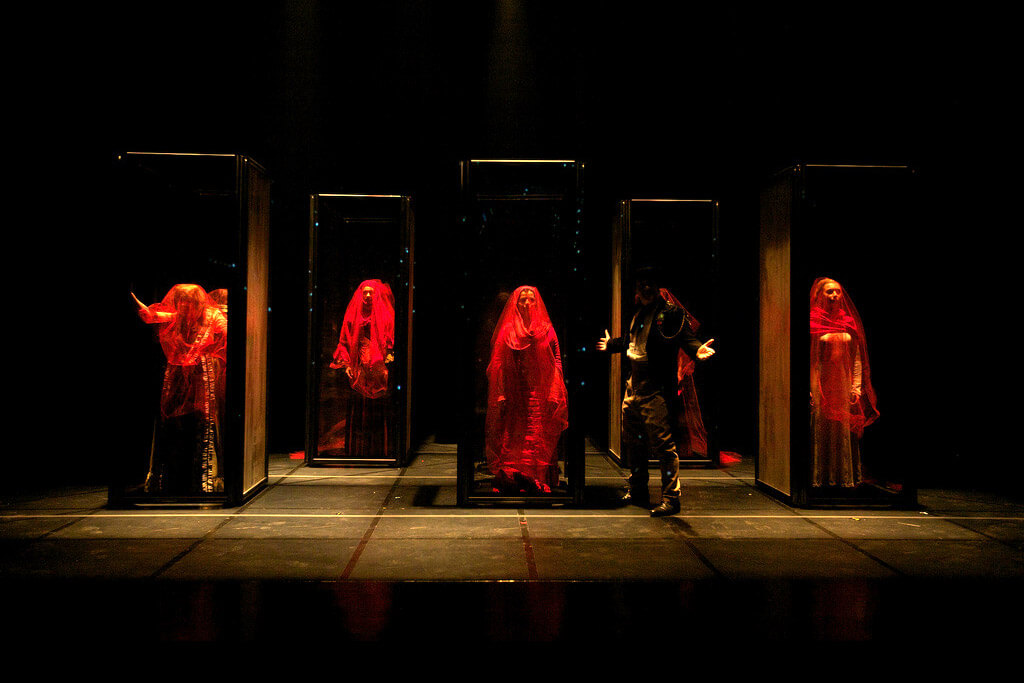 Production image from ANA showing 5 figures fress in red veils and a figure in black
