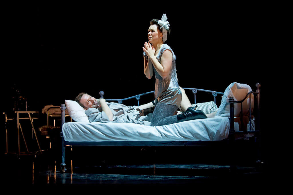 Production image from Age of Arousal showing a woman in a corset and a large bow in her hair kneeling on a bed next to someone lying in the bed straddling