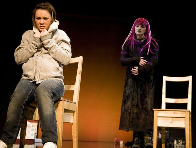 Baby Baby promotional image showing a young woman looking scared sitting in a chair she is wearing a grey zip hoody and grey jeans. Behind her stands a young woman with long pink hair and waring a long black coat