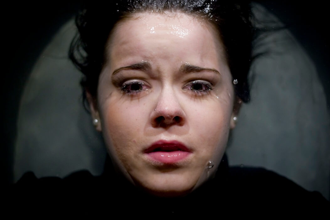 Promotional image for Dare to Care showing a closeup of a woman's face lying in watter