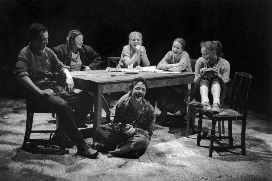 Black and white promotional image for Reel of the Hanged Man showing a group of people laughing and sitting around a wooden table with a young man sitting laughing on the floor