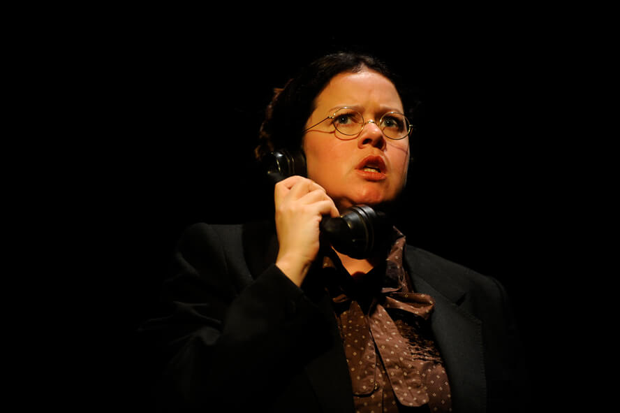 Production image of the Girls of Slender Means showing a woman talking an old fashioned phone. She is wearing round glasse, a brown and white spotted blouse and black jacket