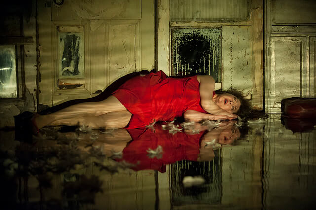 Promotional image for The Carousel showing Maureen Beattie in a red dress lying on the floor.
