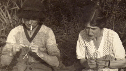 Black and white image of two women in old fashioned clothes knitting outside