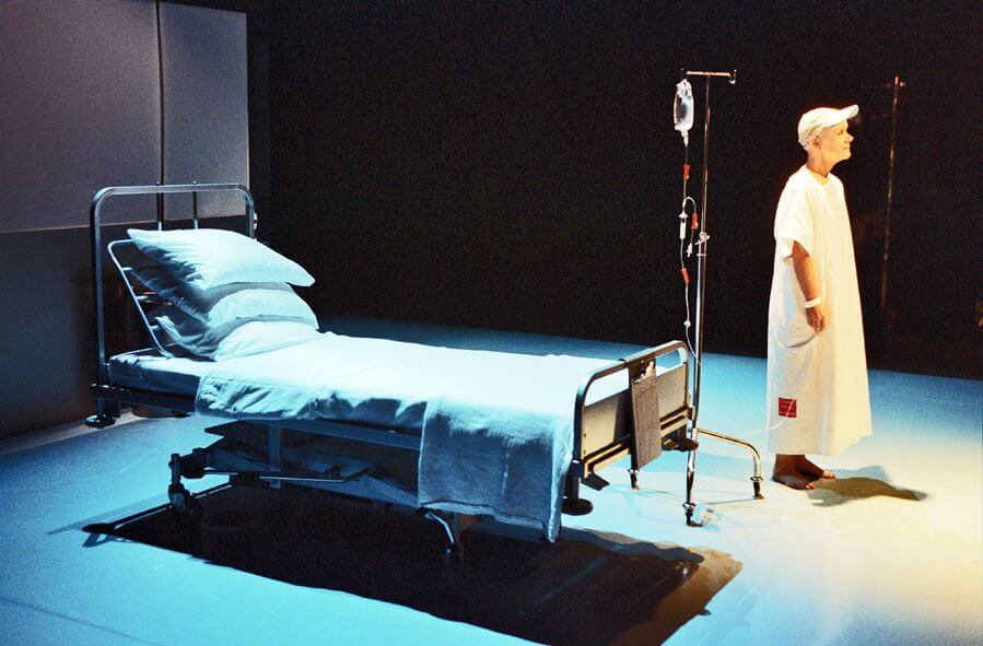 Wit promotional image showing a woman wearing a white cap and hospital gown standing on stage next to a hospital bed