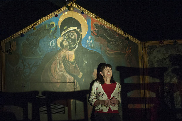 Production image from The Deliverance showing Maureen Beattie on stands on stage looking upset. Behind her is mural that looks biblical