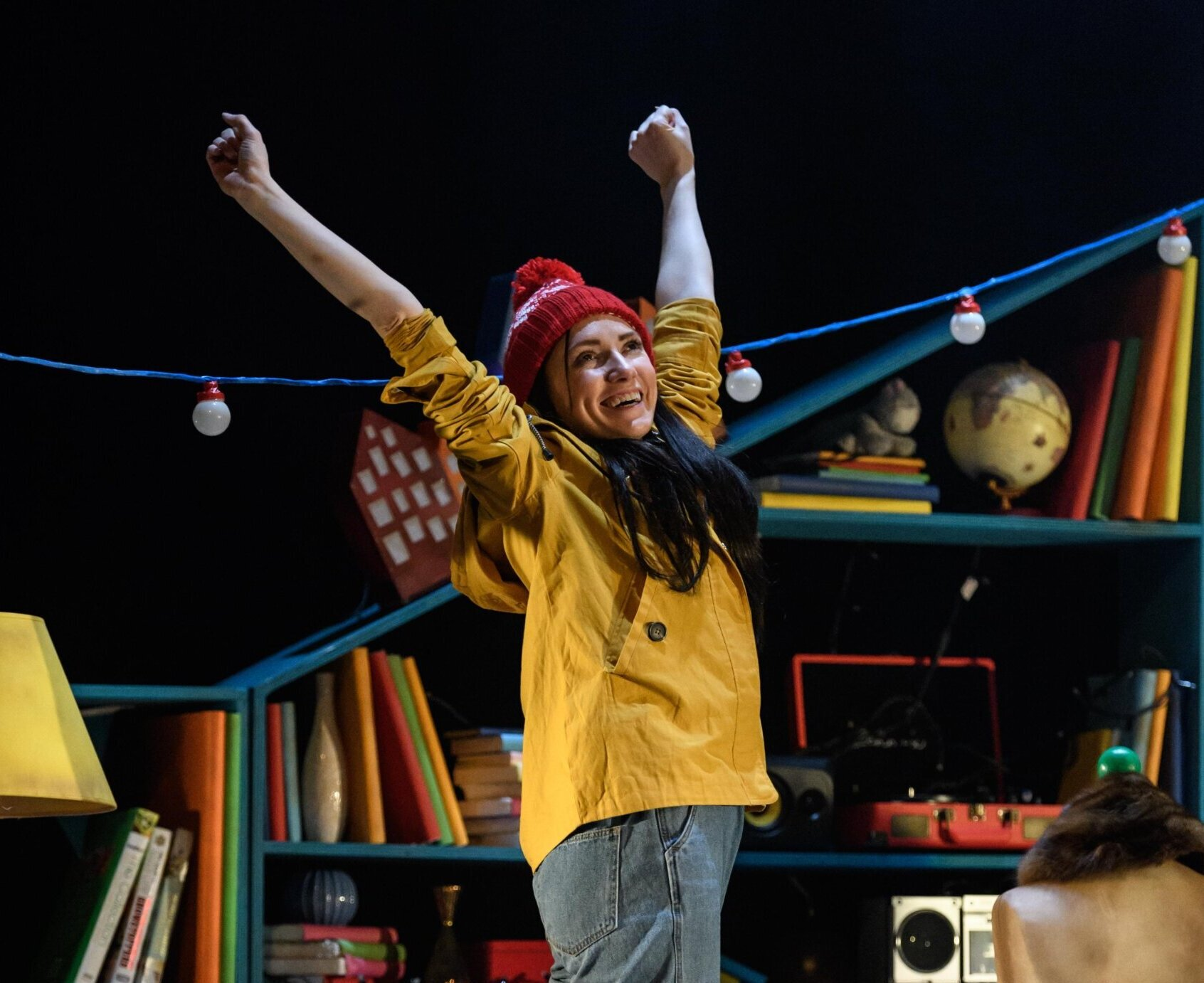 A young woman stand looking happy with her arms raised in triumph. She is wearing a yellow anorak and a red bobble hat and standing on a colourful stage