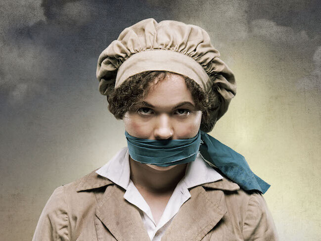 Promo image for The 306: Day showing a woman in 1940s-style workers hat and overalls with a teal gag around her lips