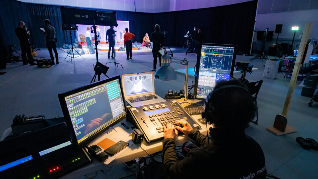 Filming of Fibres. Stage Manager is seated at a desk of screens overseeing the production. In the background, the film is being shot with the cast on stage surrounded by lights and cameras.