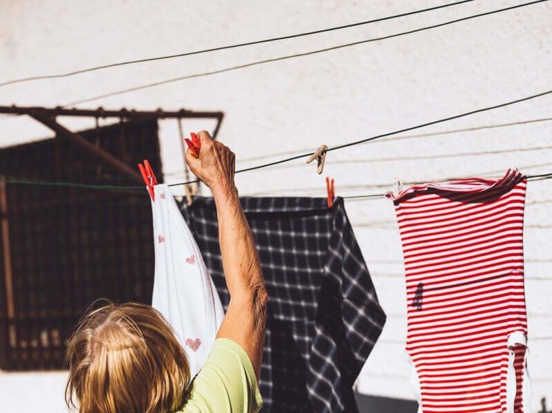 Fibres promo image showing a woman hanging out a washing on a clothes line - image taken from the back