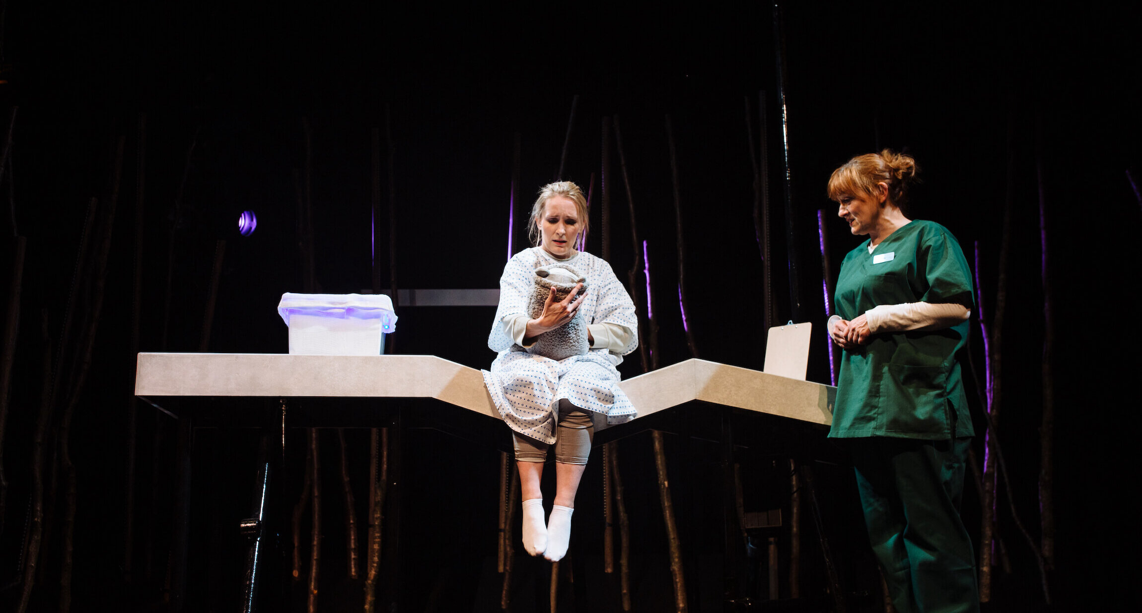 Hope & Joy production image showing a woman in green scrubs standing next to woman in hospital gown sitting on the edge of a bed holding a teddy